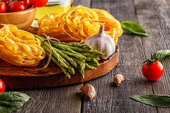 Products for cooking - fresh asparagus, pasta, olive oil. Stock Image
