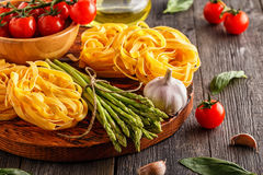 Products for cooking - fresh asparagus, pasta, olive oil. Stock Photo