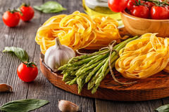 Products for cooking - fresh asparagus, pasta, olive oil. Products for cooking - fresh asparagus, pasta, tomatoes, garlic, olive oil on the old wooden Stock Photos