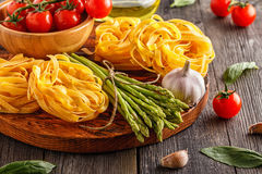 Products for cooking - fresh asparagus, pasta, olive oil. Royalty Free Stock Photos