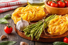 Products for cooking - fresh asparagus, pasta, olive oil. Stock Photography