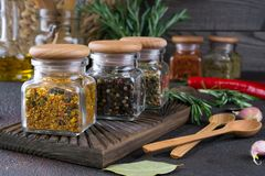 Products for cooking in kitchen, kitchen utensils, herbs, colorful dry spices in glass jars. On dark background Royalty Free Stock Images