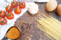 Products for cooking pasta. Tomato, egg, spaghetti, garlic, parsley, spices. Royalty Free Stock Photos