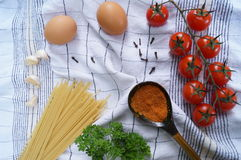 Products for cooking pasta. Tomato, egg, spaghetti, garlic, parsley, spices. Royalty Free Stock Images