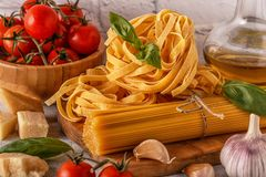 Products for cooking - pasta, tomatoes, garlic, olive oil, basil Stock Photos