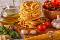Products for cooking - pasta, tomatoes, garlic, olive oil, basil Royalty Free Stock Photo