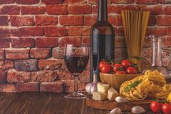 Products for cooking - pasta, tomatoes, garlic, olive oil and re. D wine. Selective focus stock photo