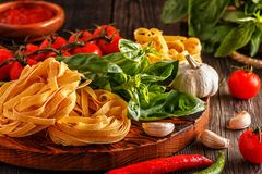 Products for cooking - pasta, tomatoes, garlic, pepper, and basi Royalty Free Stock Images