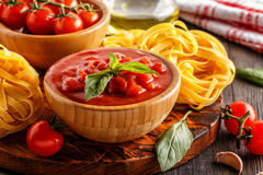 Products for cooking - tomato sauce, pasta, tomatoes, garlic. Stock Photo