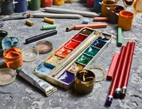 Products for drawing on a concrete table. The concept of inspiration for creation. Multicolored gouache, oil, watercolor paints stock photos