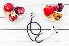 Products good for heart and blood vessels. Vegetables, fruits, nuts in heart shaped bowl near stethoscope on white. Wooden background top view royalty free stock image