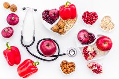 Products good for heart and blood vessels. Vegetables, fruits, nuts in heart shaped bowl near stethoscope on white. Background top view royalty free stock photos