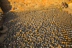 Products pottery production are dried on the street in the open sun. BHAKTAPUR, NEPAL - CIRCA DEC, 2013: Products pottery production are dried on the street in Stock Photography
