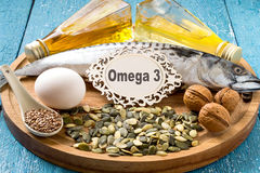 Products - source fatty acids Omega 3. (mackerel, camelina oil, rapeseed oil, organic egg, pumpkin and flax seeds, walnuts) on a round wooden board Stock Images
