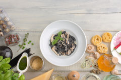 Products on textured wooden table horizontal. Other ingredients of Italian cuisine whith black pasta with mushrooms and cream  on a white wooden background stock image