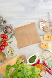 Products on textured wooden table. Other ingredients of Italian cuisine with piece kraft paper on a white wooden background royalty free stock photography