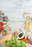 Products on textured wooden table. Other ingredients of Italian cuisine: wine, mushrooms, pasta, red pepperpesto sauce on a white wooden background royalty free stock images