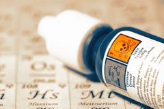 Produit chimique dans une bouteille avec une étiquette de mise en garde toxique sur la table périodique image stock