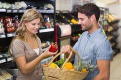 Produits alimentaires de achat de sourire de couples lumineux Photos stock