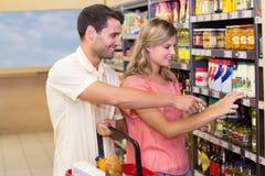Produits alimentaires de achat de sourire de couples lumineux montrant l'étagère Photo stock