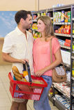 Produits alimentaires de achat de sourire de couples lumineux utilisant le panier à provisions Photos stock