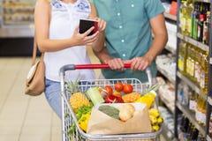 Produits alimentaires et à l'aide de achat de sourire de couples lumineux du carnet Photographie stock