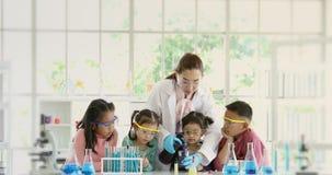 Produits chimiques de versement de professeur dans le becher dans le laboratoire banque de vidéos