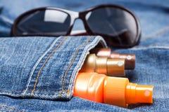 Produits cosmétiques de protection solaire dans la poche de jeans Images libres de droits