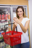 produits d'achat de femme et à l'aide de son smartphone Photo stock