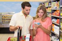 Produits de achat d'un couple lumineux utilisant le panier à provisions images libres de droits