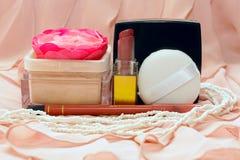 Produits de beauté sur le fond du tissu rose Photo stock