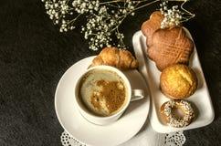 Produits de boulangerie avec la tasse blanche de café soluble Photographie stock