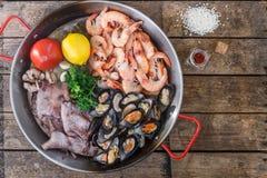 Produits de fruits de mer crus dans la casserole de Paella sur une table en bois, vue supérieure Photos libres de droits