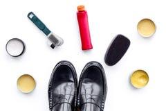 Produits de soin de chaussure Chaussures en cuir d'hommes, cirage à chaussures, brosses, cire sur la vue supérieure de fond blanc Photographie stock libre de droits