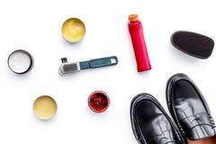 Produits de soin de chaussure Chaussures en cuir d'hommes, cirage à chaussures, brosses, cire sur la vue supérieure de fond blanc Images stock