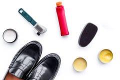Produits de soin de chaussure Chaussures en cuir d'hommes, cirage à chaussures, brosses, cire sur la vue supérieure de fond blanc Photos stock