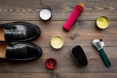 Produits de soin de chaussure Chaussures en cuir d'hommes, cirage à chaussures, brosses, cire sur la vue supérieure de fond en bo Image stock