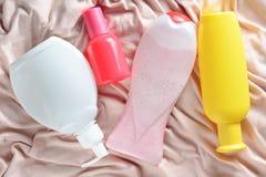 Produits pour verser et pour la beauté : shampooing, gel de douche, savon liquide, parfum sur une serviette de tissu de couleur e image libre de droits