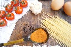 Produkte für das Kochen von Teigwaren Tomate, Ei, Spaghettis, Knoblauch, Petersilie, Gewürze Stockfotografie