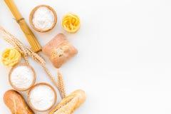 Produkte machten vom Weizenmehl Weißmehl in der Schüssel, in den Weizenähren, im frischen Brot und in den rohen Teigwaren auf Dra stockfotos