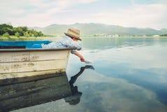 Produkteinführungspapierschiff des kleinen Jungen vom alten Boot auf dem See Lizenzfreie Stockbilder
