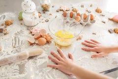 Produkter för att baka Kid& x27; s-händer lagar mat sötsaker Mjöl med deg, ägg, äggskal och kex på köksbordet fotografering för bildbyråer
