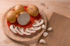 Produkter för att laga mat, champinjoner, potatisar, lökar, vitlök, örter arkivfoto