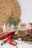 Produkter för att laga mat i kök, köksgeråd, örter, färgrika torra kryddor i glass krus Arkivfoton