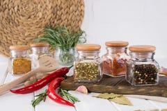 Produkter för att laga mat i kök, köksgeråd, örter, färgrika torra kryddor i glass krus Fotografering för Bildbyråer