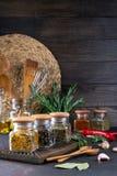 Produkter för att laga mat i kök, köksgeråd, örter, färgrika torra kryddor i glass krus på mörker arkivbild
