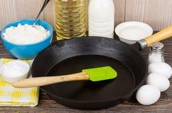Produkter för att laga mat pannkakor och järnstekpannan på tabellen Royaltyfri Fotografi