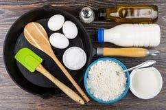 Produkter för att laga mat pannkakor och järnstekpannan på tabellen Arkivfoto