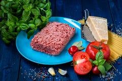 Produkter för förberedelsen av pasta Bolognese Köttfärs tomater, spagetti, basilika, parmesanost, kryddor fotografering för bildbyråer