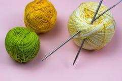 Produkter för handarbete som sticker Bollar av gult, grönt purpurfärgat garn, stickor på en rosa bakgrund fotografering för bildbyråer